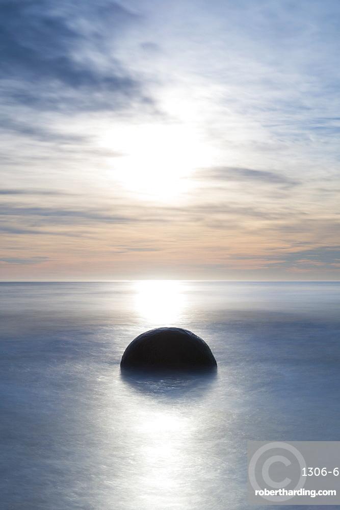 A single Moeraki Boulder at sunrise with long exposure, Moeraki Beach, Otago, South Island, New Zealand, Pacific