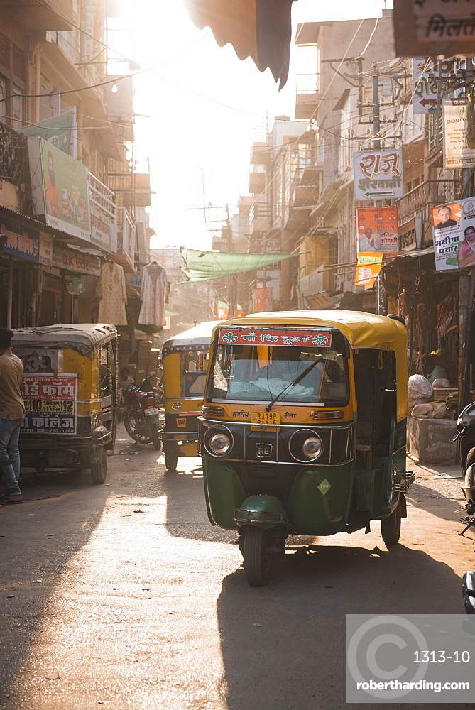 Tuk Tuks at sunset ride through the tiny streets of Jodhpur, Rajasthan, India, Asia