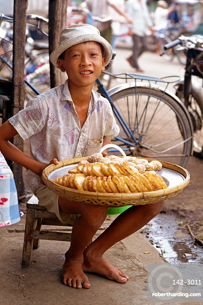 Portrait of a boy selling sweet cakes on the pavement in the town of Rach Gia in the Mekong Delta, Vietnam, Indochina, Southeast Asia, Asia