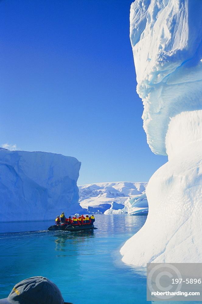 Tourists in inflatable cruising past icebergs, Antarctica