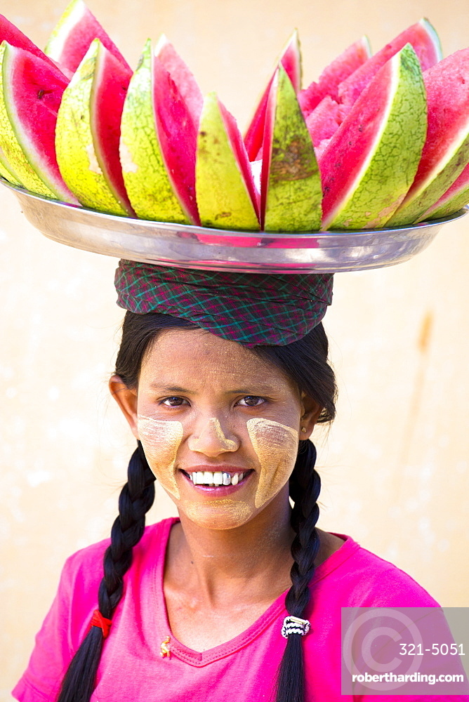 Local woman with Thanakha traditional face painting, carrying a tray of sliced watermelon on her head, Shwezigon Paya, Nyaung U, Myanmar (Burma), Asia