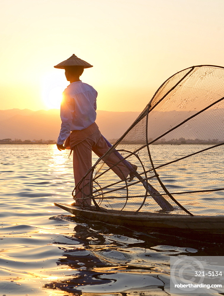 Intha 'leg rowing' fishermen sunset on Inle Lake who row traditional wooden boats using their leg and fish using nets stretched over conical bamboo frames, Inle Lake, Myanmar (Burma), Southeast Asia