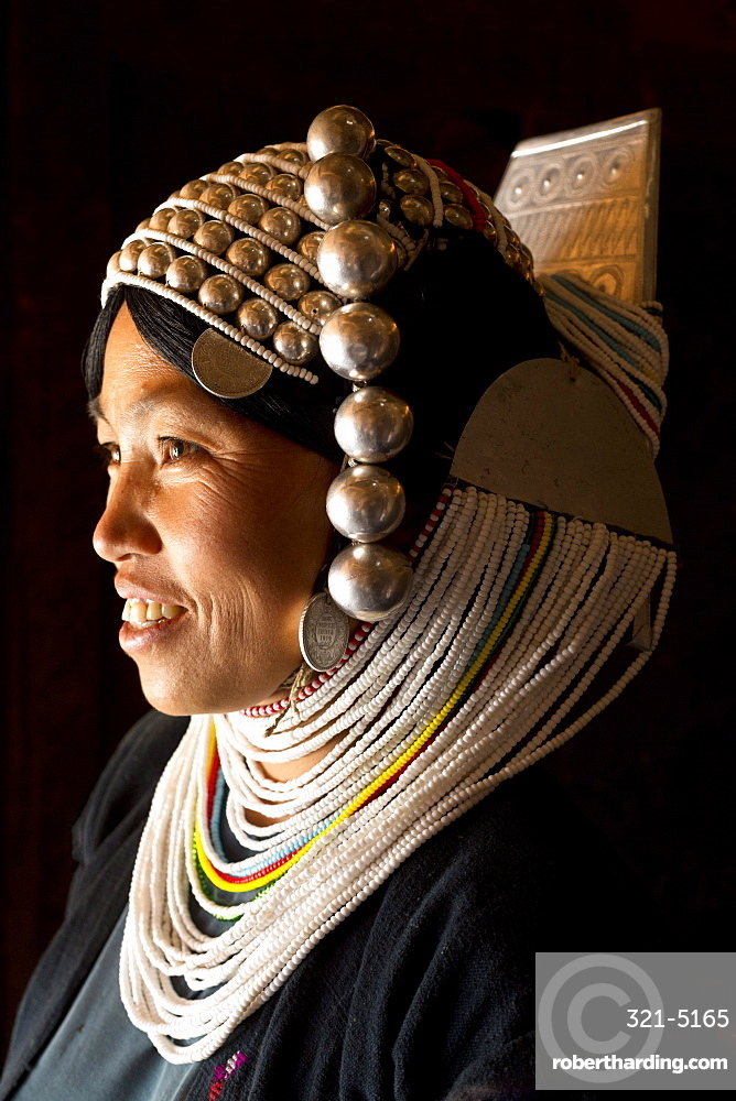 Woman of the Akha tribe in traditional dress including a headdress of heavy silver baubles, in a hill village near Kengtung (Kyaingtong), Shan State, Myanmar (Burma), Asia