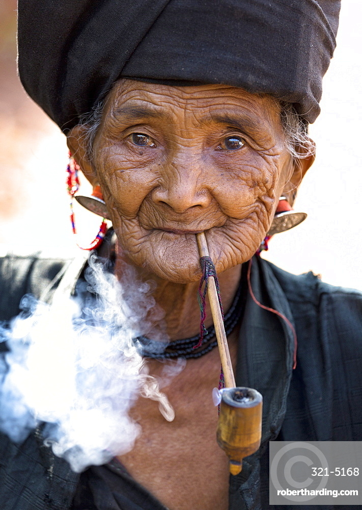 Woman of the Ann tribe in traditional black dress smoking a pipe outside a hill village near Kengtung (Kyaingtong), Shan State, Myanmar (Burma), Asia