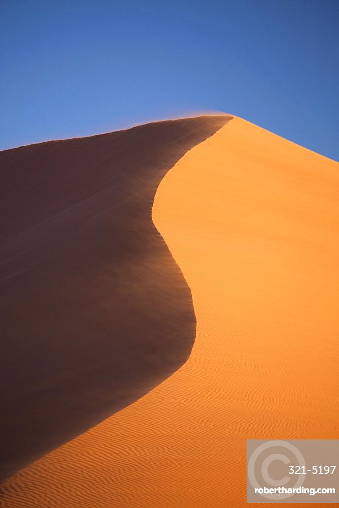 The orange sand and snaking ridge of Elim Dune against blue sky, Namib Desert near Sesriem, Namib Naukluft Park, Namibia, Africa