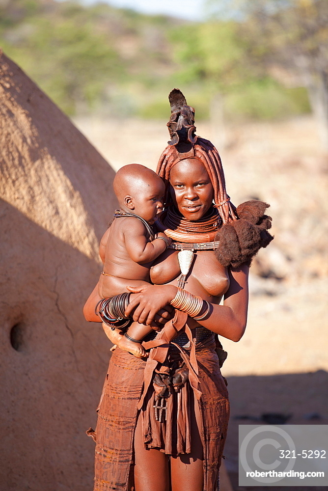Young Himba woman, with baby, wearing traditional dress and jewellery and with her skin covered in Otjize, a mixture of butterfat and ochre, Kunene Region, formerly Kaokoland, Namibia, Africa