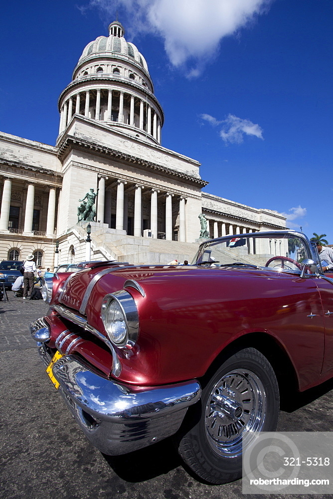 Red vintage American car parked opposite The Capitolio, Havana Centro, Havana, Cuba, West Indies, Central America
