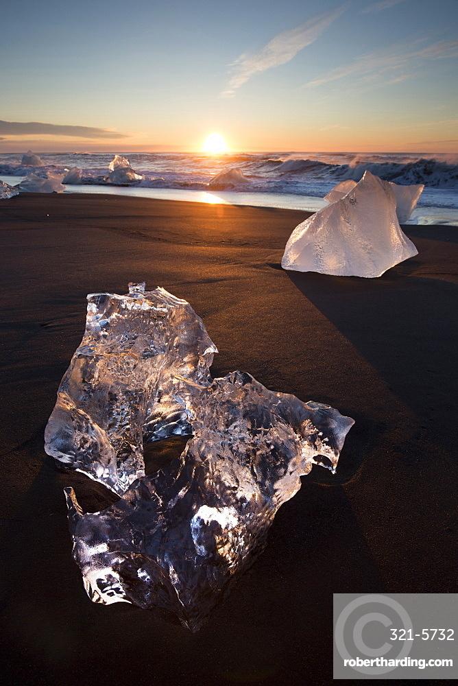 Glassy pieces of ice on volcanic black sand beach at sunrise, near Jokulsarlon Lagoon, South Iceland, Polar Regions