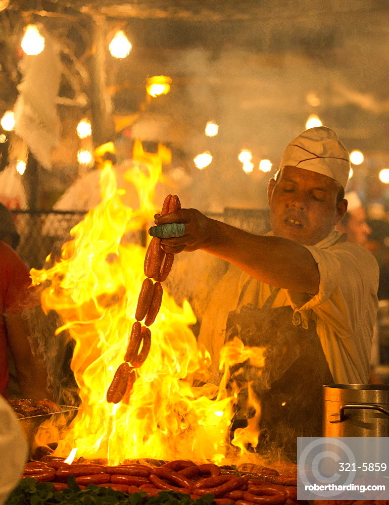 Local man cooking sausages on open flame at one of the food stalls in the Djemaa el Fna, Marrakech, Morocco, North Africa, Africa
