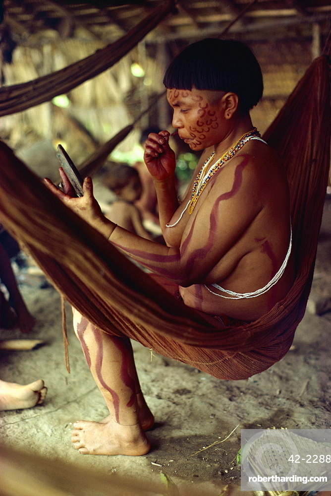 Yanomami Indian women with mirror, painting her face, Brazil, South America