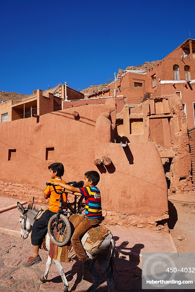 Boy with donkey gives bicyclist a lift in 1500 year old traditional village of red mud brick houses, Abyaneh, Iran, Middle East