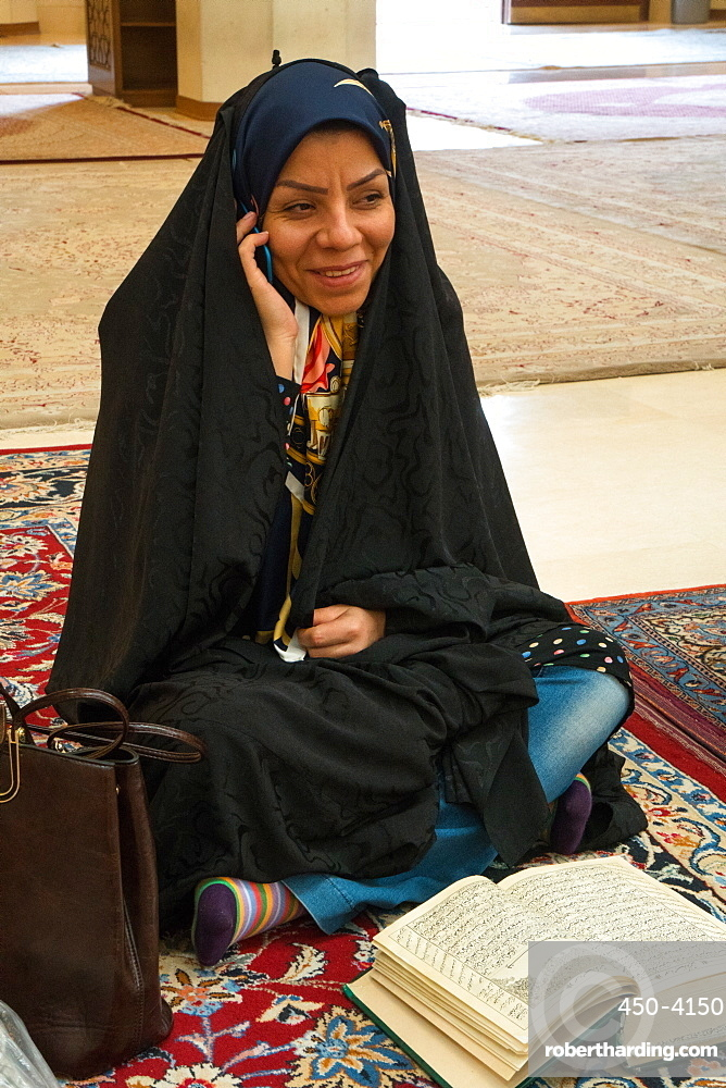 Young woman torn between her mobile and her religious reading, Aramgah-e Shah-e Cheragh (Mausoleum of the King of Light), Shiraz, Iran, Middle East