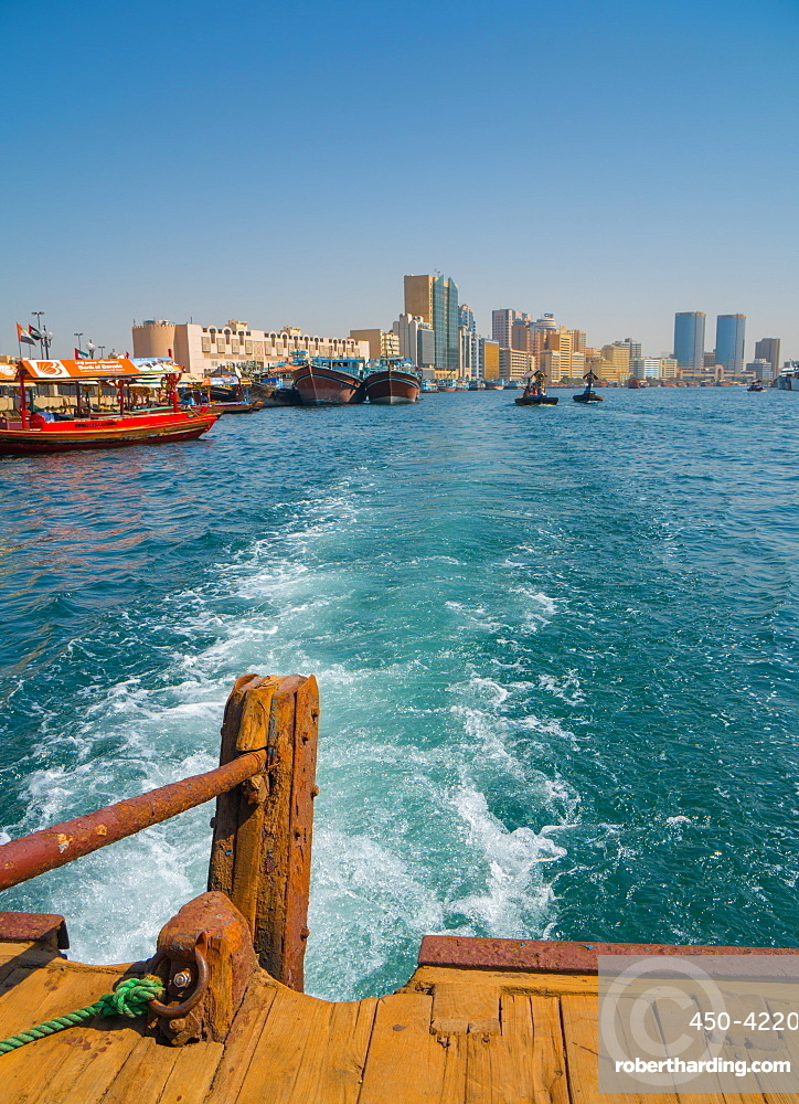 Modern Dubai cityscape disappears in the wake of an old water taxi speeding past the dhow harbour up Dubai Creek, Dubai, United Arab Emirates, Middle East