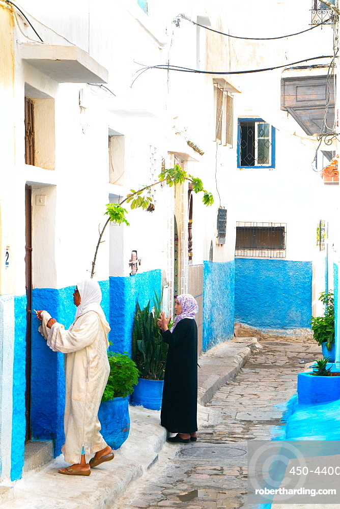Two woman in local dress at neighbouring front doors, Kasbah des Oudaias, UNESCO World Heritage Site, Rabat, Morocco, North Africa, Africa