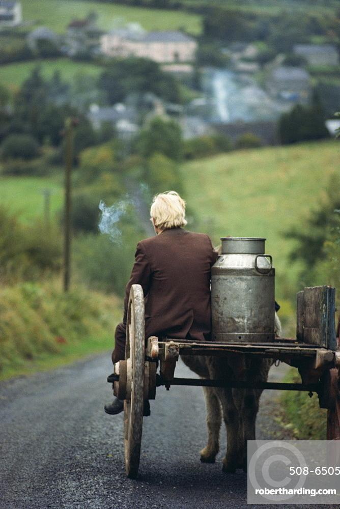 Figure riding cart with milk churn, Arigna, Shannon River, County Leitrim, Connacht, Republic of Ireland, Europe