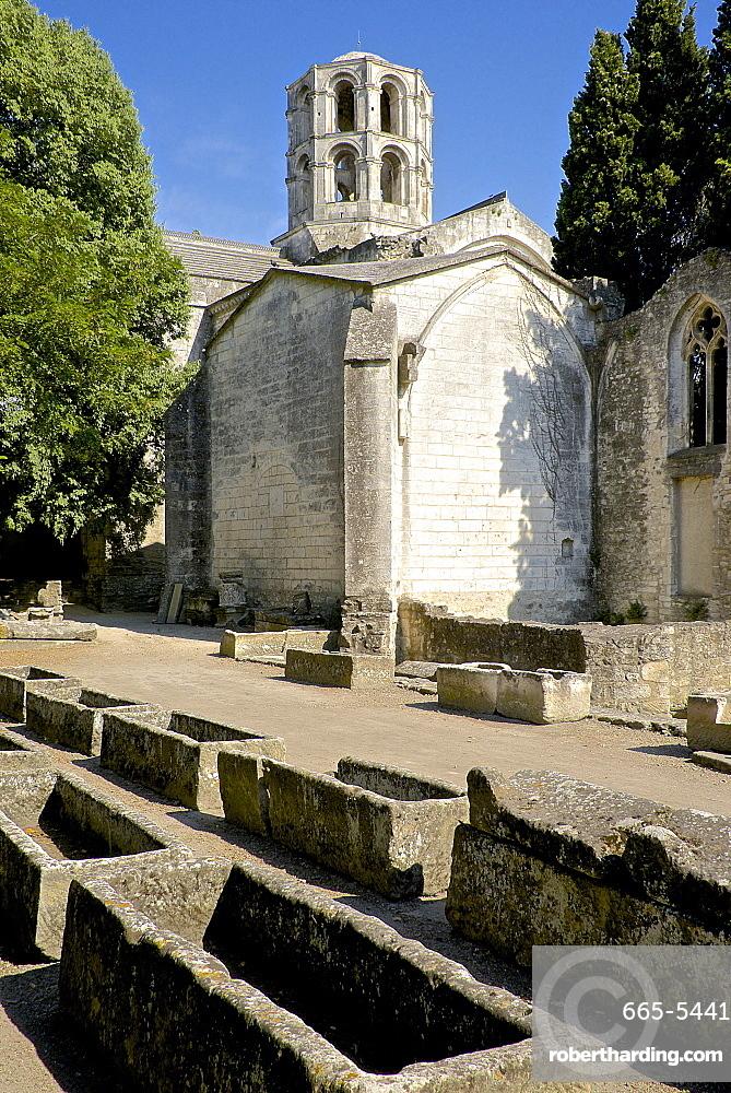 Gallo-roman sarcophagi, Alyscamps, gallo-roman necropolis, and the lantern steeple of the 12th century Saint Honorat church, Arles, Bouches du Rhone, Provence, France, Europe