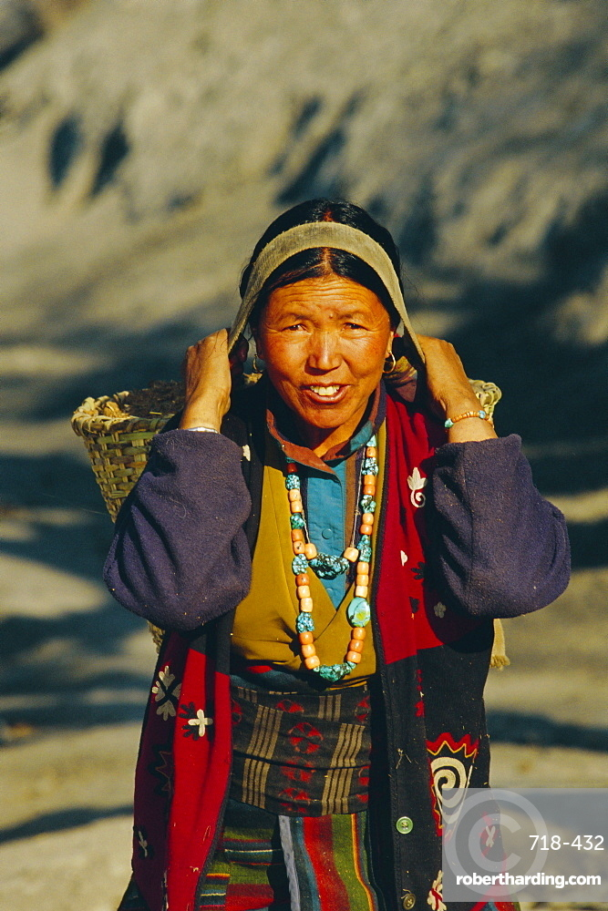 Gurung woman carrying goods in a woven basket (doto) on her back, near MUKtinath, Nepal