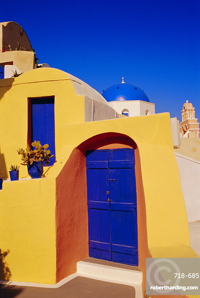 Blue and yellow traditional house with churches in the background, Oia village, Oia, Santorini (Thira), Cyclades Islands, Greece