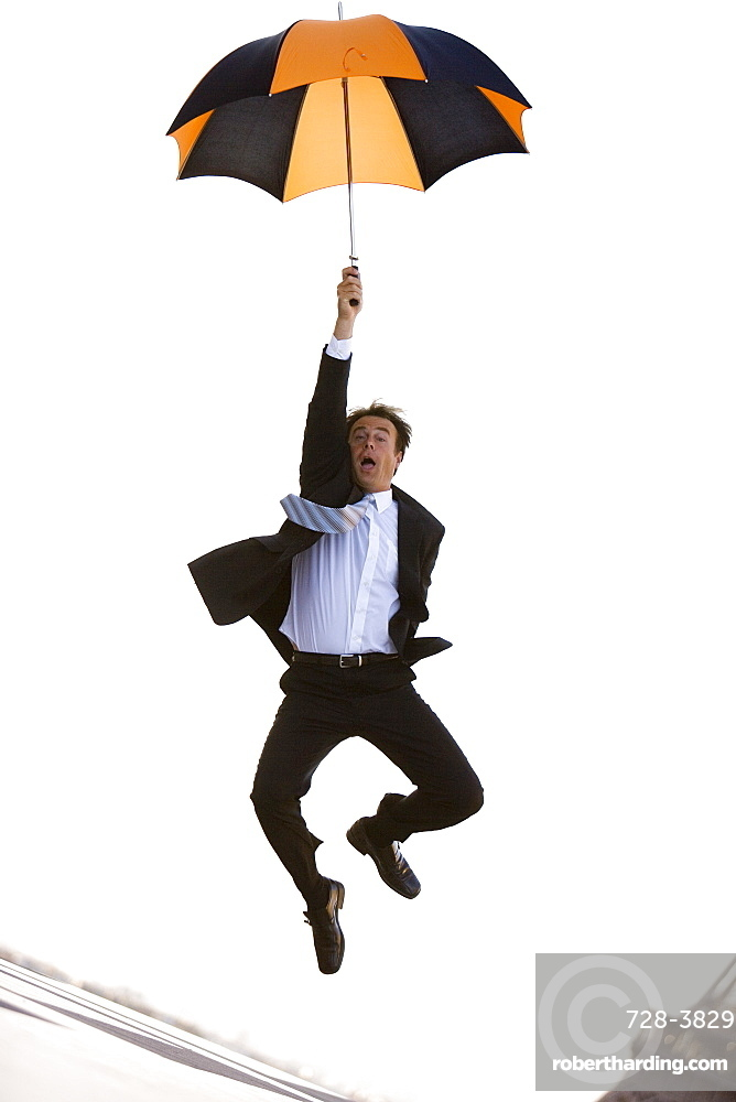 Business man with umbrella jumping in the air, Paris, France, Europe