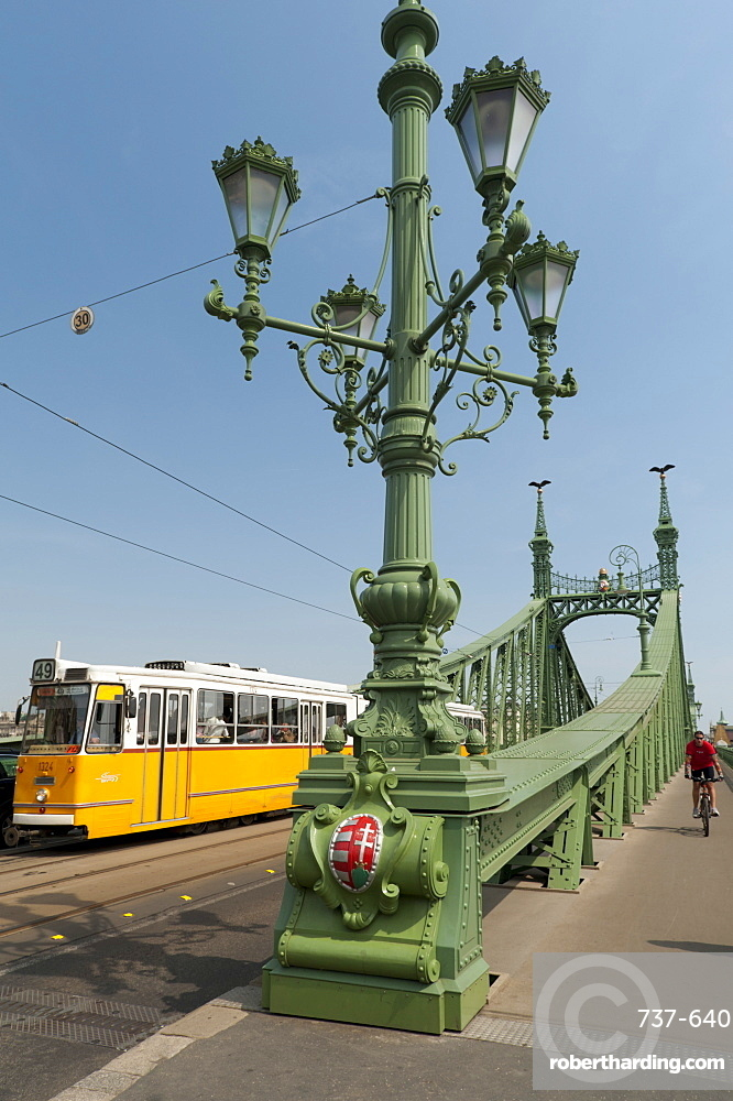 Tram and cyclist on Independence Bridge spanning Danube River, Budapest, Hungary, Europe