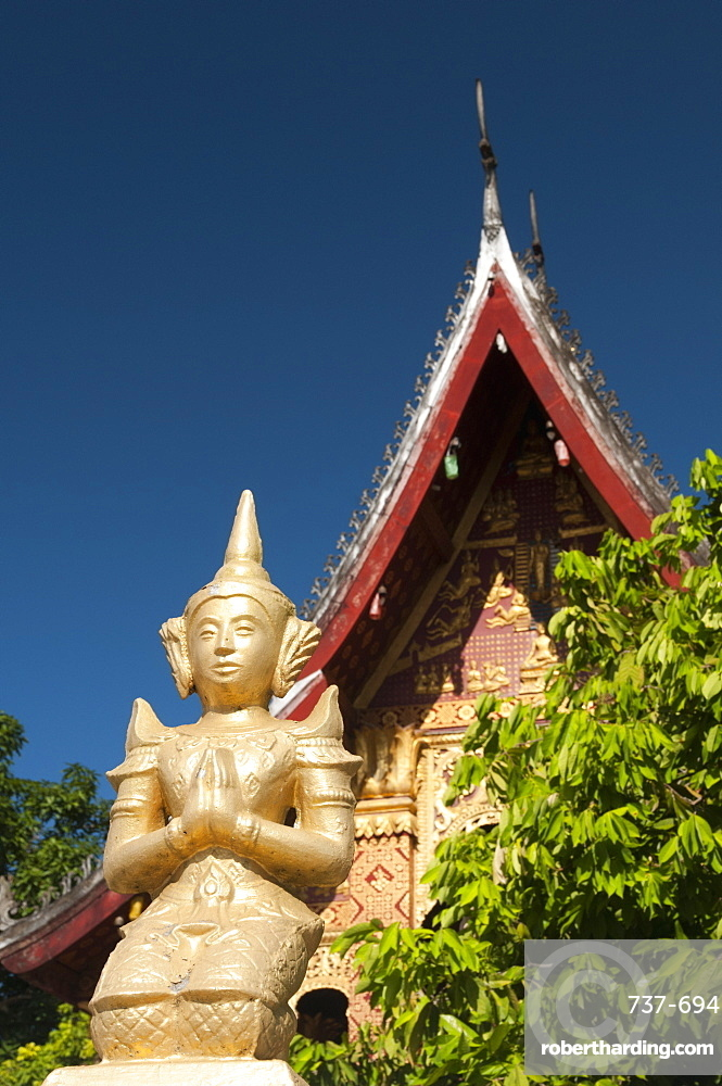 Statue of a kneeling figure praying in front of Temple of Wat Sop Sickharam, Luang Prabang, Laos, Indochina, Southeast Asia, Asia