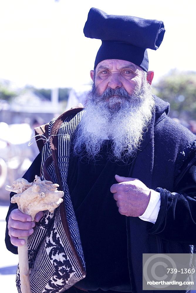 Man wearing the traditional Berritta Sardinian hat and carring the traditional double Sardinian sac, St. Antioco celebrations, Sant'Antioco,Sardinia, Italy, Europe
