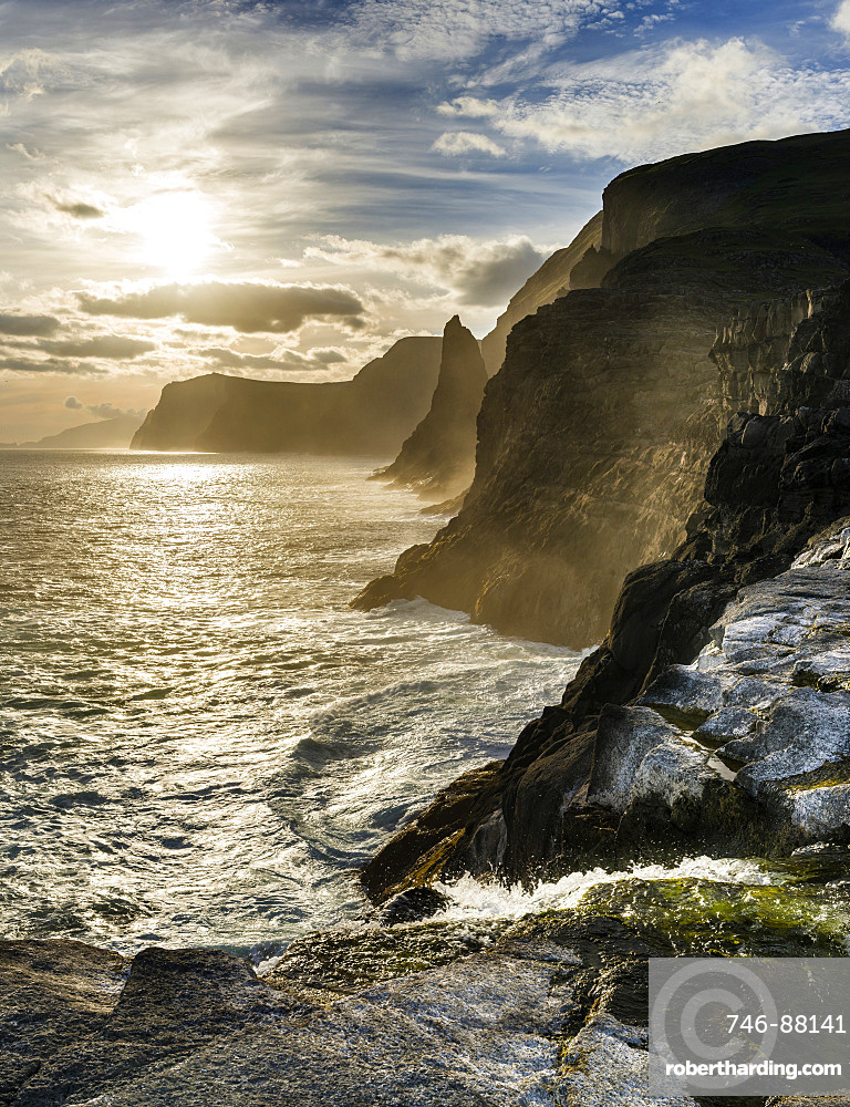 The west coast near Traelanipa with waterfall Bosdalafossur at sunset.  The island Vagar, part of the Faroe Islands in the North Atlantic.  Europe, Northern Europe, Denmark, Faroe Islands