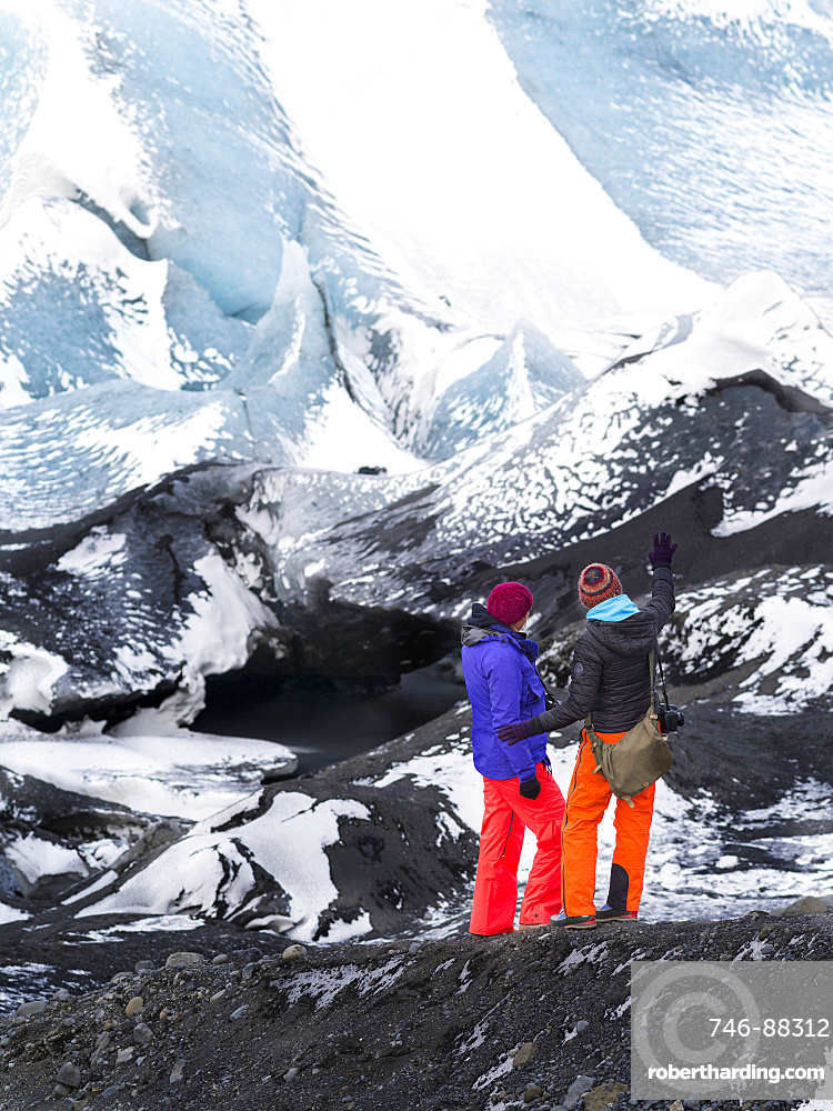 Glacier Solheimajoekull in the south of Iceland, a outlet glacier of glacie  Myrdalsjoekull. Two tourists watching the glacier. europe, northern europe, scandinavia, iceland,  February