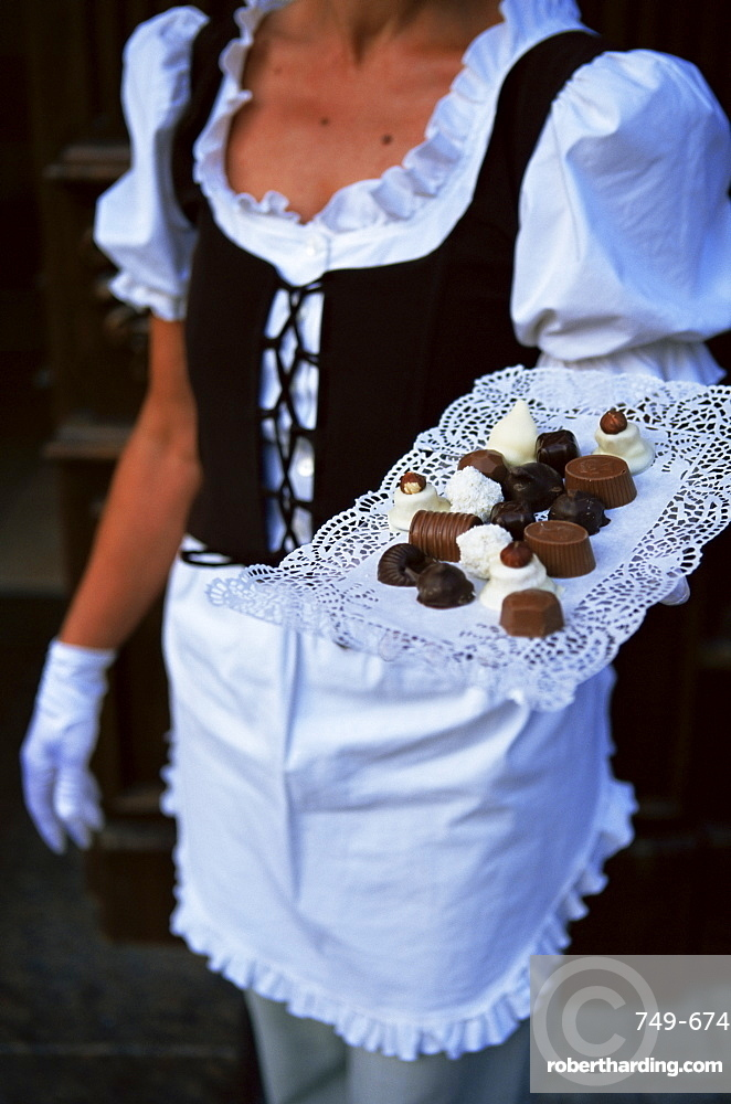 Waitress carrying tray of chocolate, Vilnius, Lithuania, Baltic States, Europe