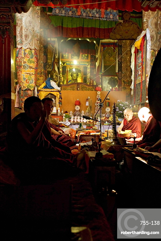 Shaft of light falls on Tibetan Buddhist monks, Meru Nyingba monastery, Bharkor, Lhasa, Tibet, China, Asia