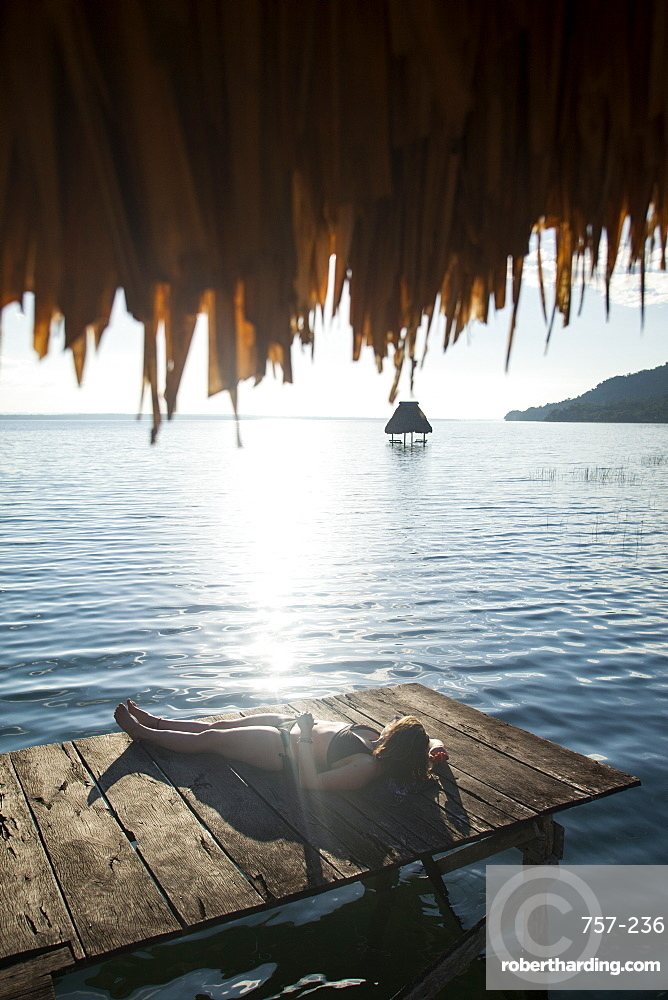 Woman relaxing on dock, El Remate, Lago Peten Itza, Guatemala, Central America