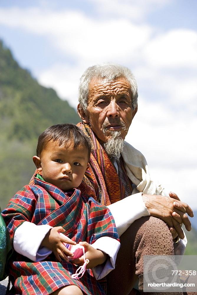 Old man and little boy at Buddhist festival (Tsechu), Haa Valley, Bhutan, Asia
