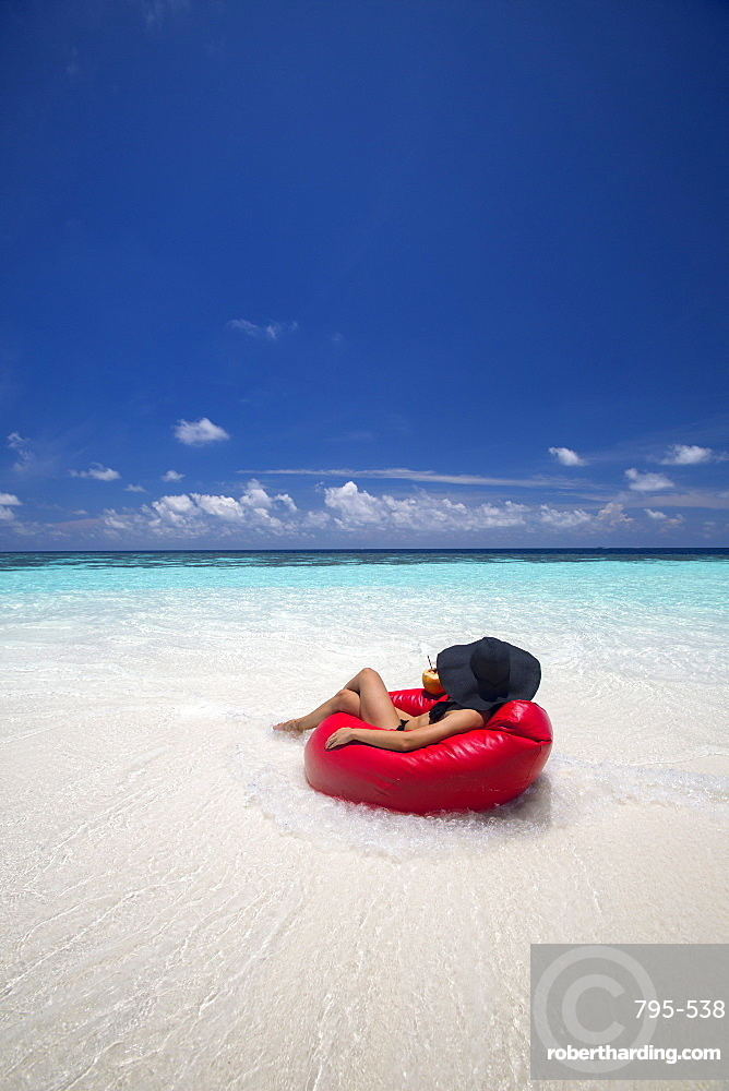 Woman relaxing on the beach, Maldives, Indian Ocean, Asia