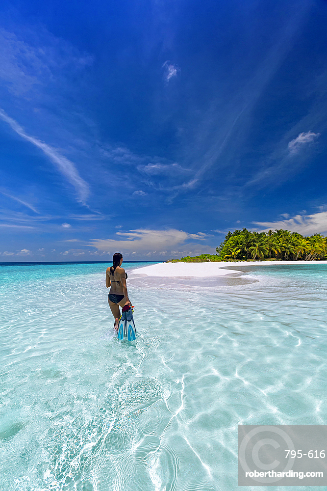 Woman with snorkelling gear on tropical beach, The Maldives, Indian Ocean, Asia