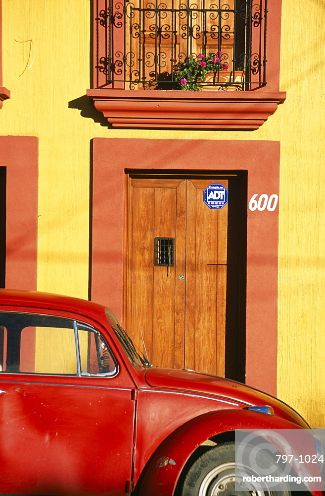 MEXICO Oaxaca Oxaca City Partly seen red volkswagon beetle outside yellow building with wooden door and window shutters in orange painted frames.
