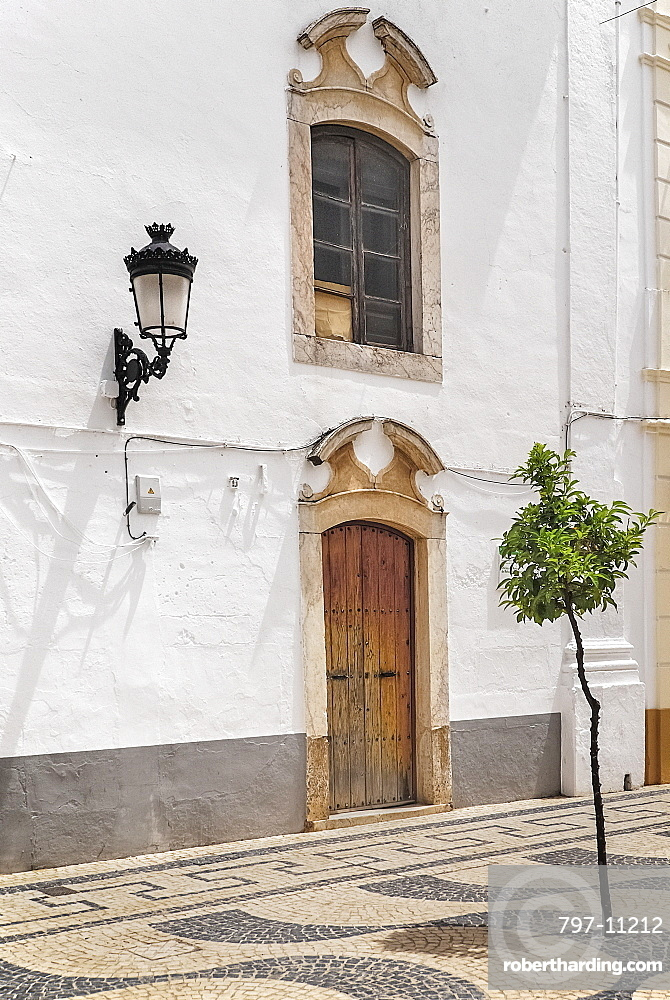 Spain, Extremadura, Olivenza, Typical building with street lamp fixed to wall.