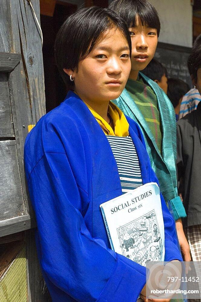 Bhutan, Mongar, Portrait of a Bhutanese school girl holding Social Studies textbook.