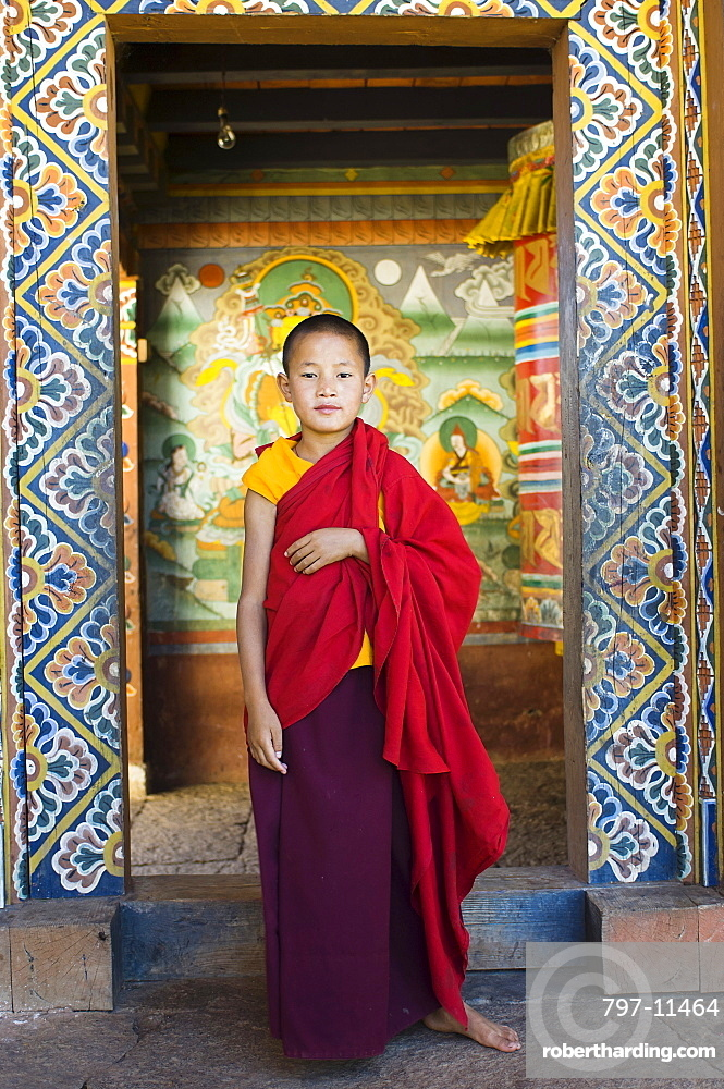 Bhutan, Chimi Lakhang, Young novice monk standing in doorway of Chimi Lakhang temple in the old capital.