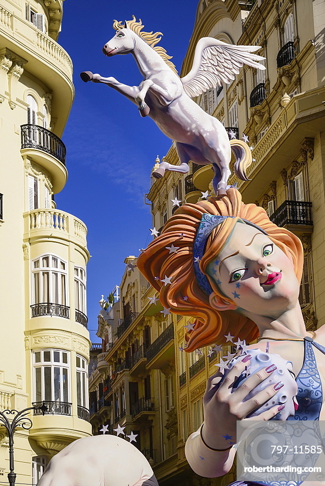 Spain, Valencia Province, Valencia, Female Papier Mache figure with a horse on her head in the street during Las Fallas festival.