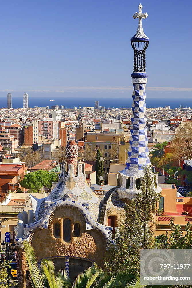 Spain, Catalunya, Barcelona, Parc Guell by Antoni Gaudi, the Administration Lodge at the park's entrance with the city and sea in the background.