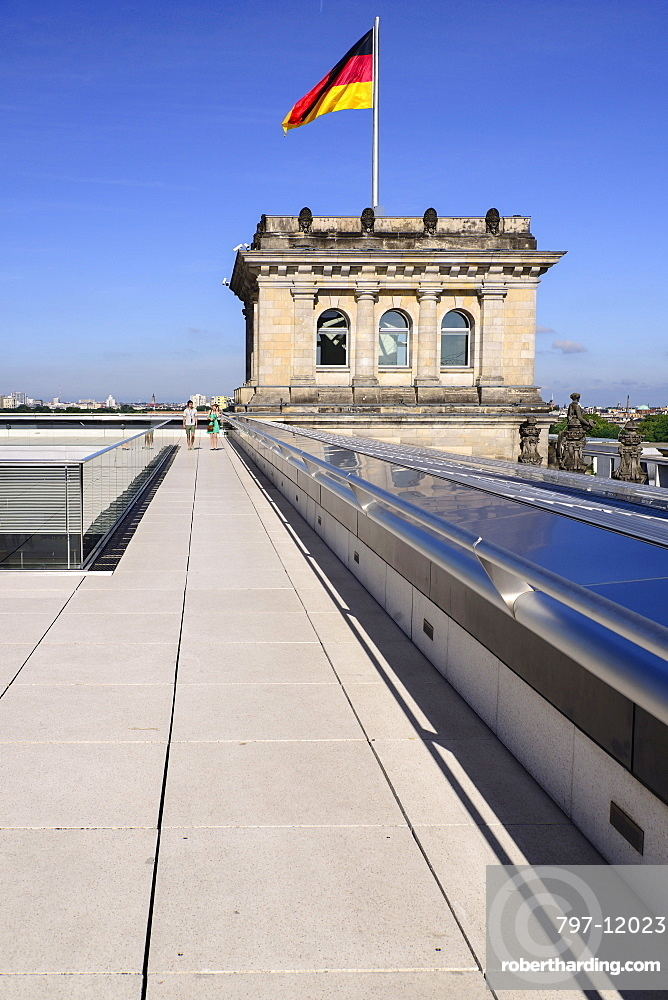 Germany, Berlin, German flag fluttering on a corner tower of the Reichstag building as seen from the rooftop terrace with two tourists strolling.