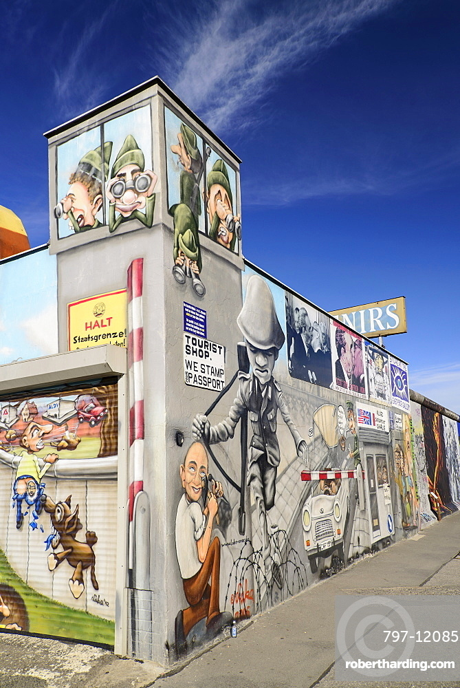 Germany, Berlin, The East Side Gallery, a 1.3 km long section of the Berlin Wall, Wall paintings and signs advertising Souvenirs and Tourist Shop.