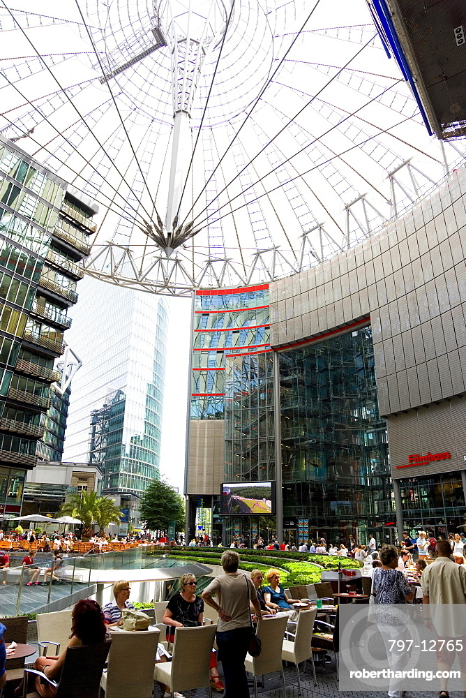 Germany, Berlin, Mitte, Potsdamer Platz, The Sony Centre designed by architect Helmut Jahn with the canopy over the central Forum of restaurants, offices, cinemas, shops and apartments with people eating at tables.