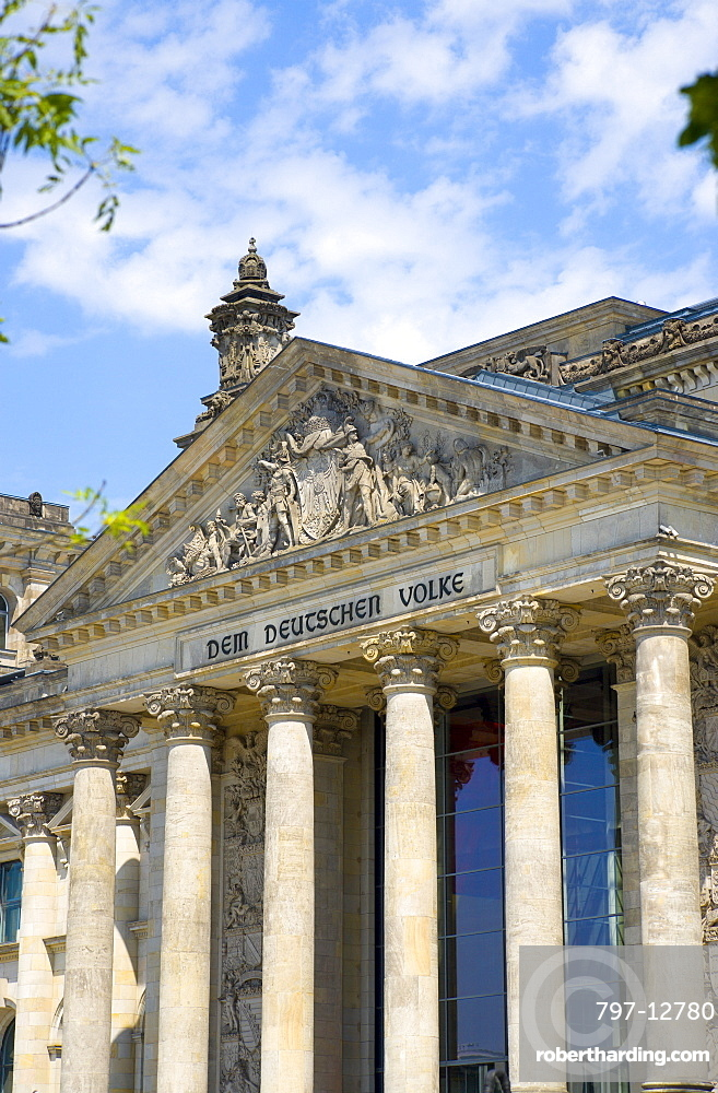 Germany, Berlin, Mitte, The Reichstag building in Tiergarten with the inscrption Dem Deucschen Volke, For the German People, on the facade above the columns at the entrance.