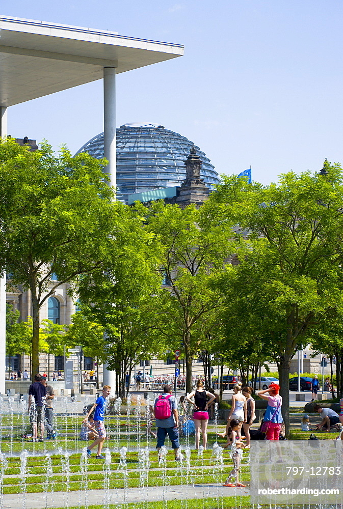 Germany, Berlin, Mitte, people cooling off in the water fountains in front of the Paul Loebe Haus by architect Stephan Braunfels housing the offices of the parliamentary committees of the Bundestag with the glass dome of the Reichstag building beyond.