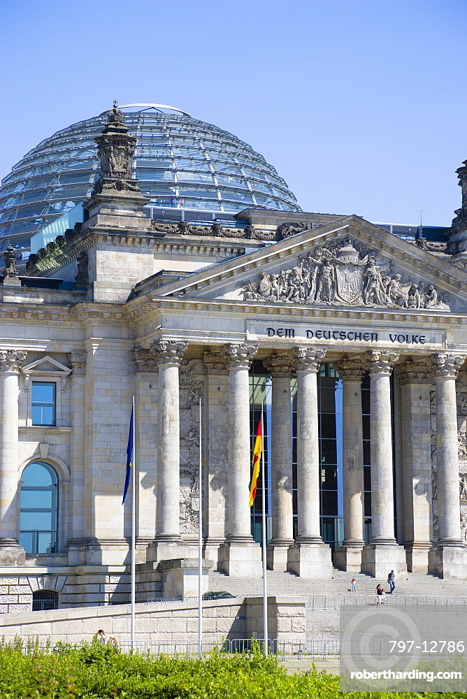 Germany, Berlin, Mitte, The Reichstag building in Tiergarten with the inscrption Dem Deucschen Volke, For the German People, on the facade above the columns at the entrance with Norman Foster's glass roof dome behind.