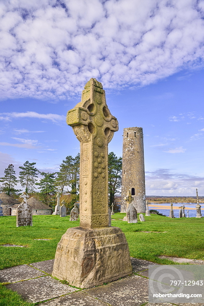 Ireland, County Offaly, Clonmacnoise Monastic Settlement, South Cross and Round Tower with River Shannon in the background.