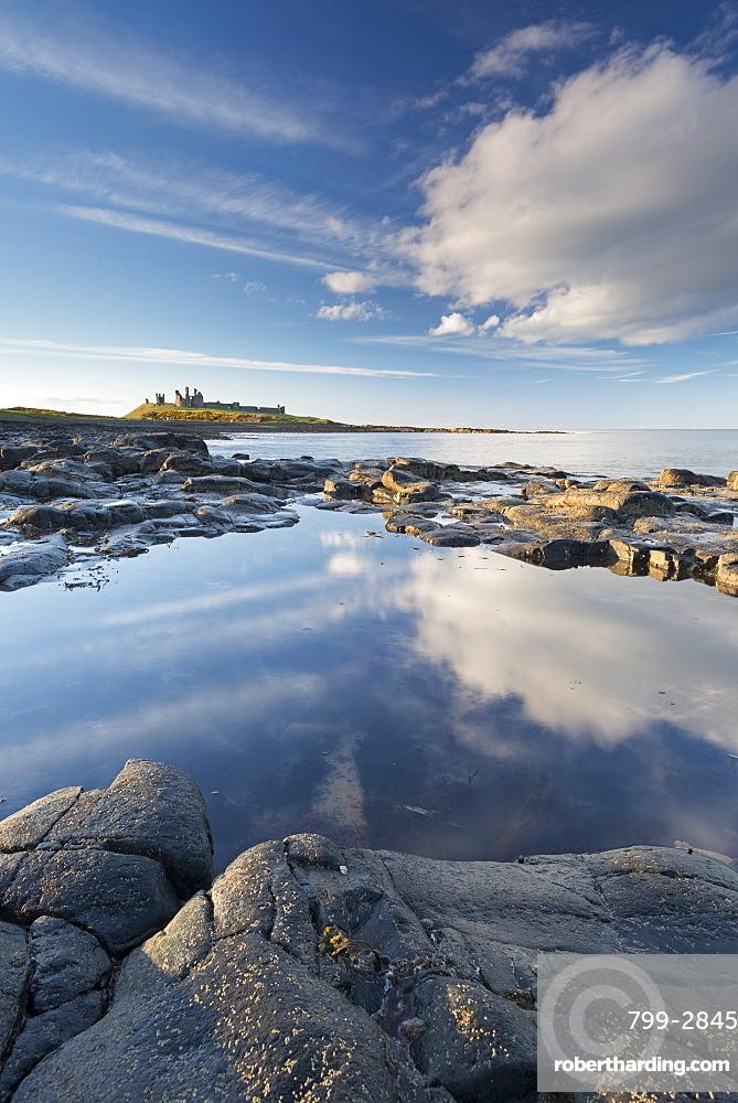 Rocky coastline with rockpools near Dunstanburgh Castle, Craster, Northumberland, England, United Kingdom, Europe