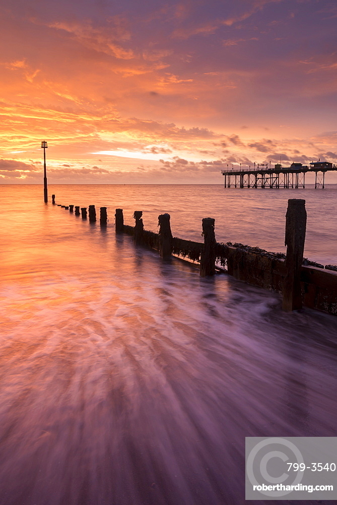 Beautiful colourful sunrise above the wooden groynes and pier at Teignmouth in Devon, England, United Kingdom, Europe