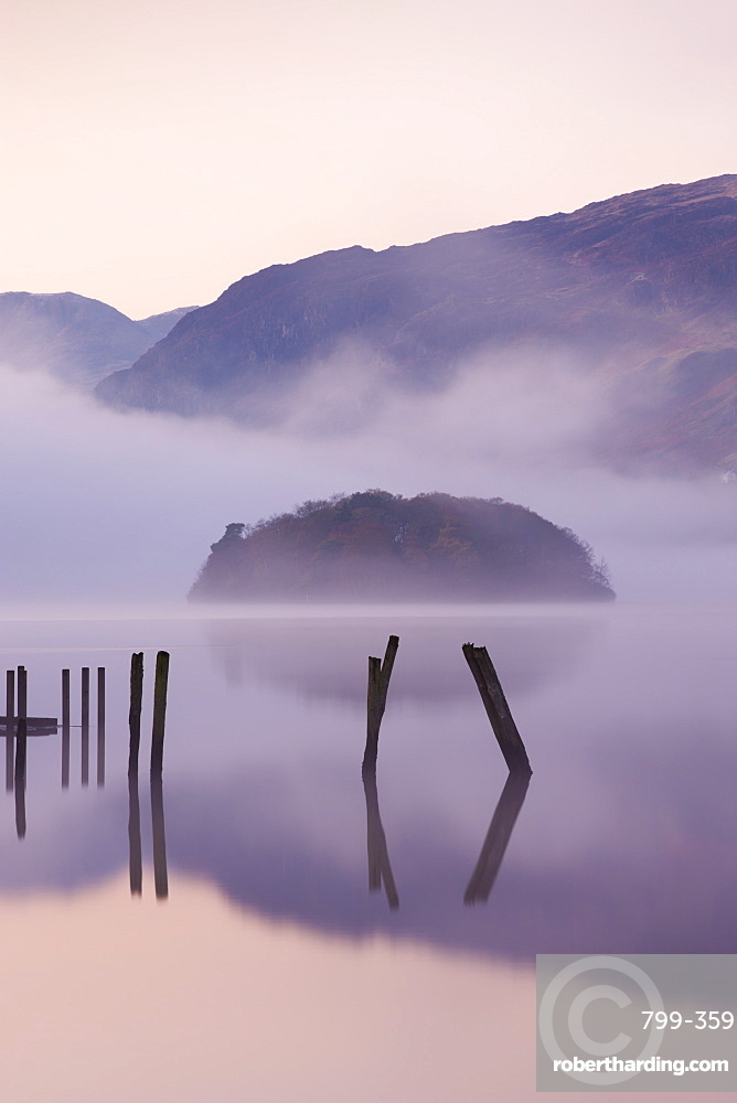 Old wooden jetty and St. Herbert's Island on Derwent Water at dawn on a misty autumn morning, Lake District National Park, Cumbria, England, United Kingdom, Europe
